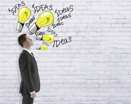 storming: Side view of young businessman in suit looking at creative light bulb sketches on white brick background. ideas concept