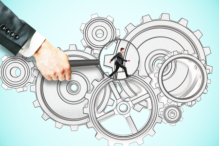 Hand holding magnifier over tiny businessman running on abstract cogwheel sketch. Blue background. Teamwork concept