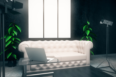side lighting: Side view of dark interior with blank posters, white leather sofa, laptop on coffee table and professional lighting equipment. Mock up, 3D Rendering