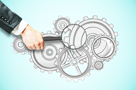 Businessman hand holding magnifier over cogwheel sketch on light blue background. Research concept Stock Photo