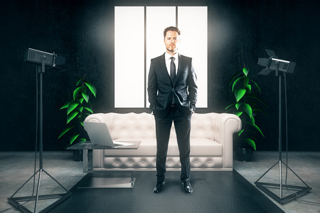 professional lighting: Confident businessman with hands in pockets standing in dark interior with professional lighting equipment, laptop and blank posters. 3D Rendering Stock Photo