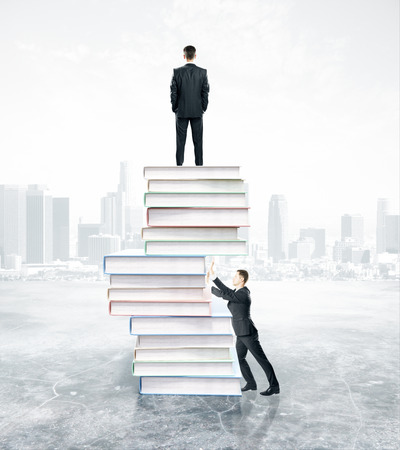 pushing: Businesspeople standing on and pushing abstract pile of books on city background. Competition concept