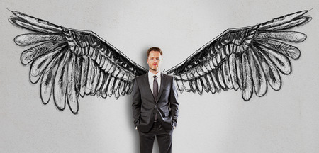Handsome businessman in suit on concrete background with creative drawn wings. Freedom concept