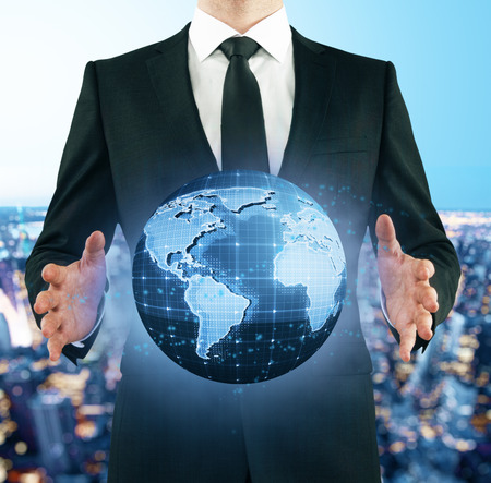 Businessman in suit holding abstract digital terrestrial globe on city background. International business concept. 3D Rendering