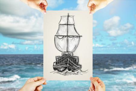 Quattro mani di sesso maschile in possesso di foglio di carta con il disegno a matita creativa di nave sul cielo blu e sfondo del mare. Vela e concetto di viaggio