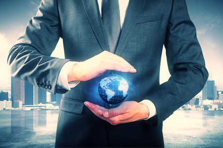 globe  the terrestrial ball: Businessman in suit holding abstract digital terrestrial globe on city background. Global business concept Stock Photo