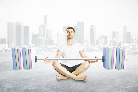 Meditating young man holding abstract dumbbell with books instead of plates on city background. Education concept Фото со стока