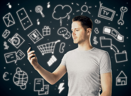 using smartphone: Handsome young man using smartphone on dark background with various drawings. Social media concept
