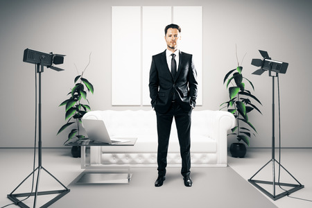 professional lighting: Confident businessman with hands in pockets standing in bright interior with professional lighting equipment, laptop and blank posters. 3D Rendering