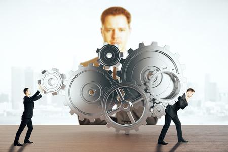 supervisión: Dos hombres de negocios empujando y arrastrando el mecanismo de engranaje abstracta en el fondo de la ciudad luz con otro hombre de negocios mirando. concepto de supervisión. Representación 3D Foto de archivo