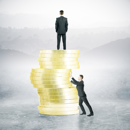 Businessman pushing abstract golden coin pile that anoter person is standing on. Landscape background. Business competition concept