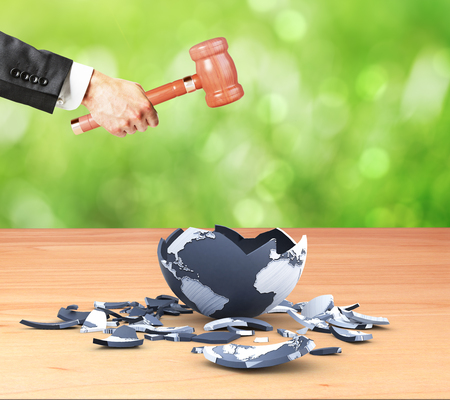 destruction: Businessman hand cracking terrestrial globe with wooden hammer on green background. World destruction concept. 3D Rendering