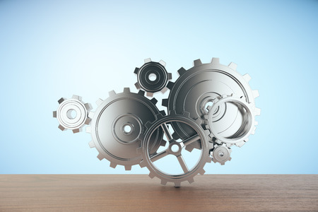 wooden work: Wooden surface with abstract gear mechanism on light blue background. Team work concept. 3D Rendering