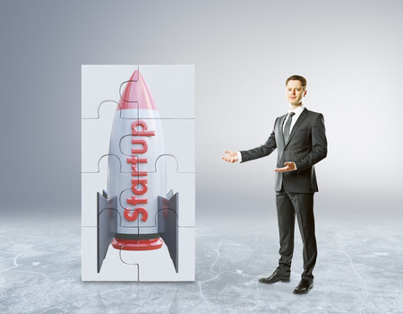 concrete block: Young businessman showing abstract rocket ship puzzle on concrete background. Project start up and development process. 3D Rendering