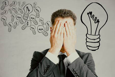 covering the face: Businessman covering face with palms on grey background with creative lamp drawings. Idea concept