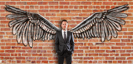 Young businessman in suit with creative drawn wings on red brick wall background