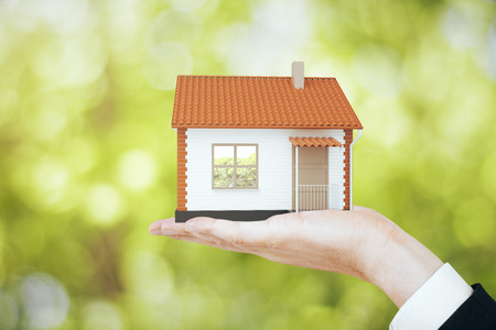 Hand holding small house model on blurry green background. Real estate, property and mortgage concept. 3D Rendering Stock Photo