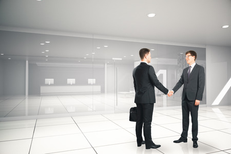 Two handsome businesspeople shaking hands in modern business interior. Partnership concept. 3D Rendering