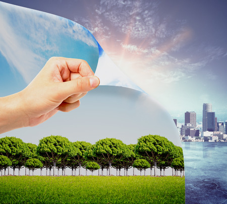 Abstract image of hand flipping page with landscape, opening page with city. Urbanization concept Stock Photo