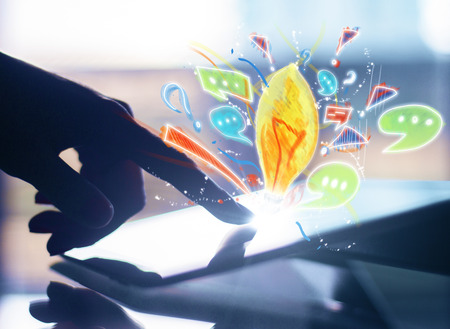 Hand using tablet with creative drawn light bulb and communication icons. Creative idea concept