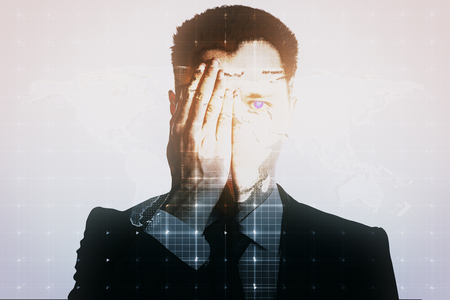 one eye: Young man closing one eye with hand on light mesh background with map