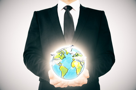 hand holding globe: Businessman holding creative globe sketch on light background. Environment protection concept