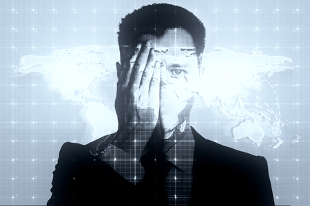 one eye: Young businessman closing one eye with hand on light mesh background with map