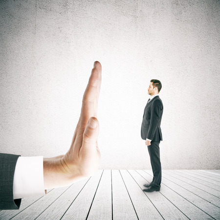 denial: Tiny businessman in suit standing against human palm on concrete background. Denial concept