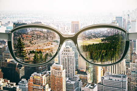urbanization: Close up of abstract glasses with landscape view on city background. Vision concept. 3D Rendering