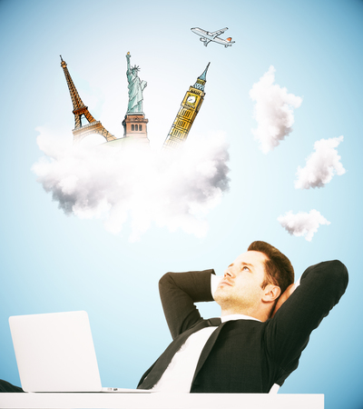 Relaxing young businessman at workplace dreaming about holidays on blue backgroud. Vacation concept Stock Photo