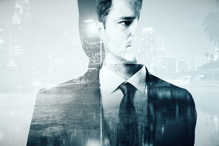 Abstract portrait of handsome young businessman on city background. Double exposure