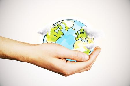 globe terrestre dessin: Une main tenant créatif globe terrestre dessiné avec des nuages ??sur fond clair. Eco concept de