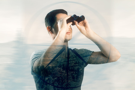 using binoculars: Young caucasian guy using binoculars on creative background with compass. Double exposure. Direction concept Stock Photo