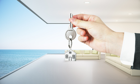 Man holding key with house keychain on modern lounge interior background with sea view. 3D Rendering. Real estate and mortgage concept