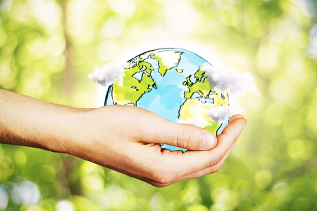 globe terrestre dessin: Hand holding creative drawn terrestrial globe with clouds on blurry green background. Eco concept