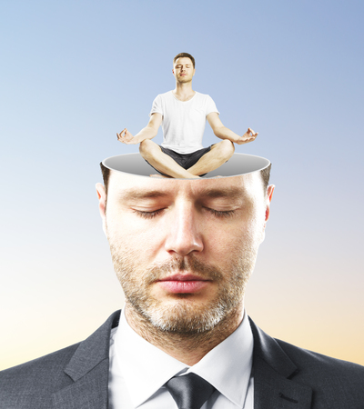 pondering: Portrait of handsome caucasian businessman with closed eyes and abstract meditating man miniature inside head on blue background. Relaxation concept Stock Photo
