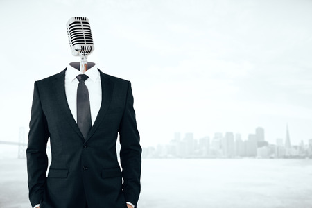 Mic headed businessman on city background with copy space.