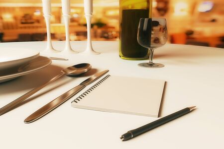 Close up of dining table with blank spiral notepad, candles, wine, cutlery and other items. 3D Rendering Stock Photo