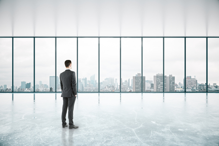 unfurnished: Thoughtful businessman standing in spacious unfurnished concrete interior with no view. 3D Rendering Stock Photo