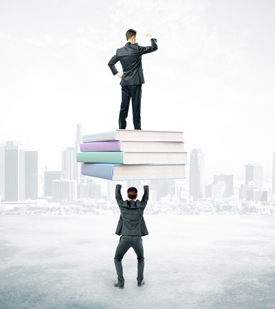 book concept: Businessmen holding and standing on book stack. City background. Education and teamwork concept