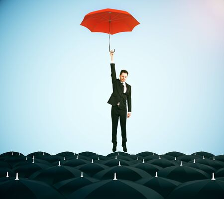 best security: Young businessman with red umbrella flying above black umbrellas on blue background. Leadership concept. 3D Rendering