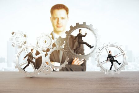 partnership security: Man watching tiny businessmen running inside iron cogwheels. Teamwork and supervision concept