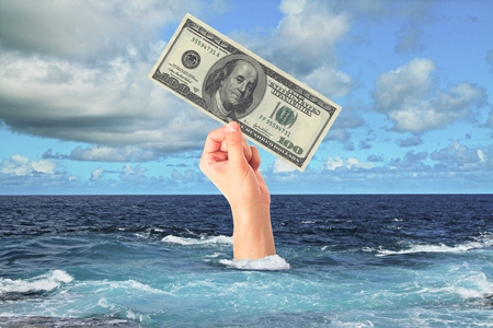 profundity: Hand with dollar bill sticking out of ocean. Sky background. Finance and risk concept Stock Photo
