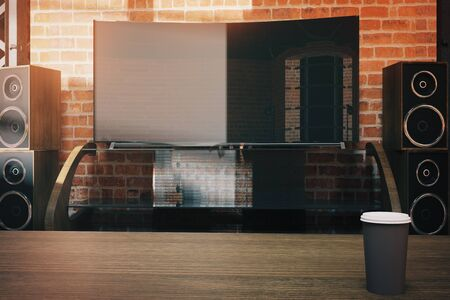 speakers desk: Front view of modern flat TV screen with loudspeakers and coffee cup on red brick wall background. Mock up, 3D Rendering