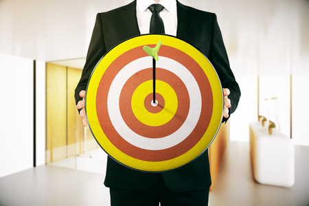 Businessman holding dartboard with arrow in the middle. Modern interior background. Aiming concept. 3D Rendering Stock Photo