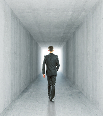 businessman walking: Businessman walking in concrete tunnel interior with bright light. 3D Rendering Stock Photo