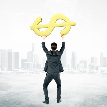 rick: Back view of businessman in suit holding golden dollar sign on city background Financial growth concept
