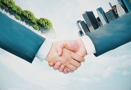 Handshake of hands with abstract trees and buildings. Business concept