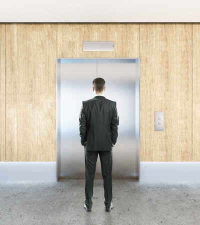 lift gate: Businessman in interior with silver elevator, wooden wall, concrete floor and ceiling. Success concept. 3D Rendering