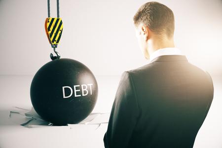 repossession: Debt concept. Sad businessman with wrecking ball